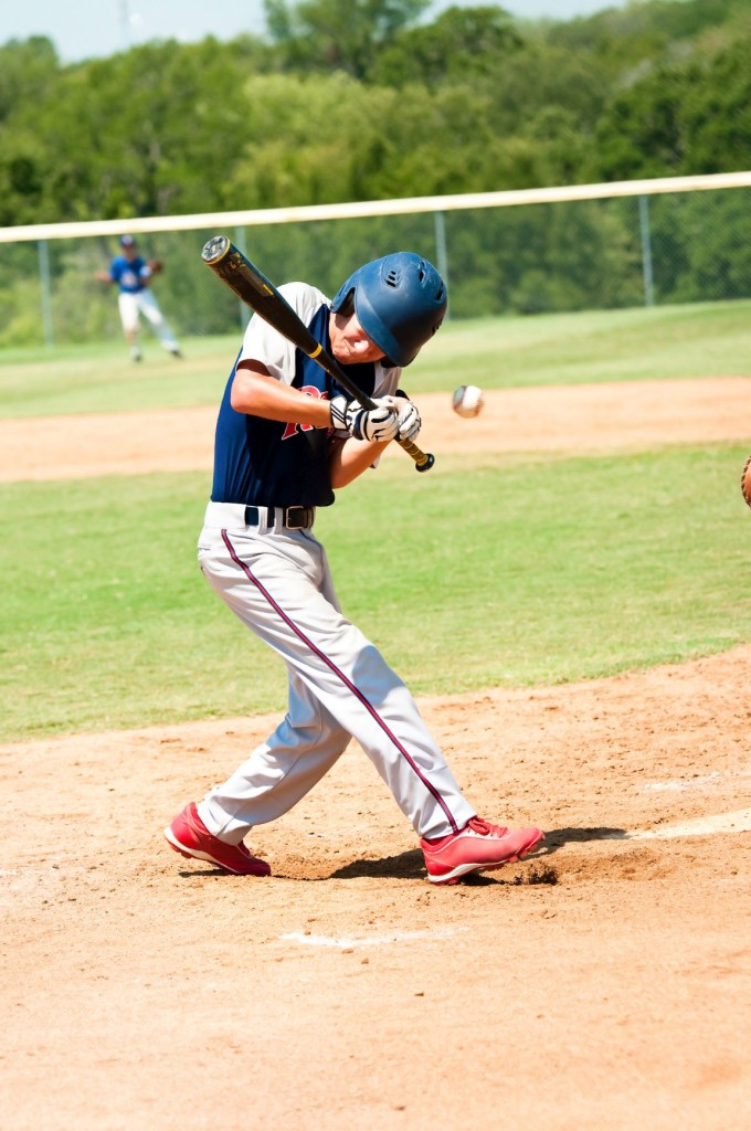 Teen baseball player getting hit by baseball during a game.
